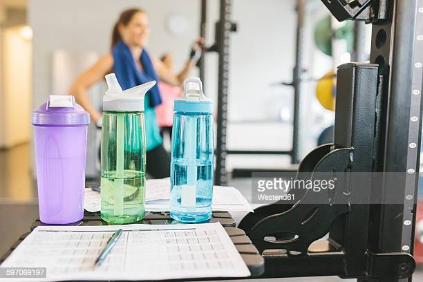 Shaker bottles with woman working out in the background