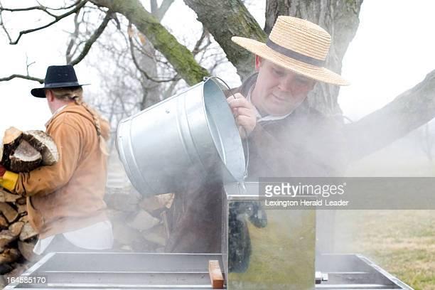 Shaker Village Historic Interpreter Philip McIntosh of Harrodsburg center pours sap from a sap pail into the evaporator as Shaker Village Historic...