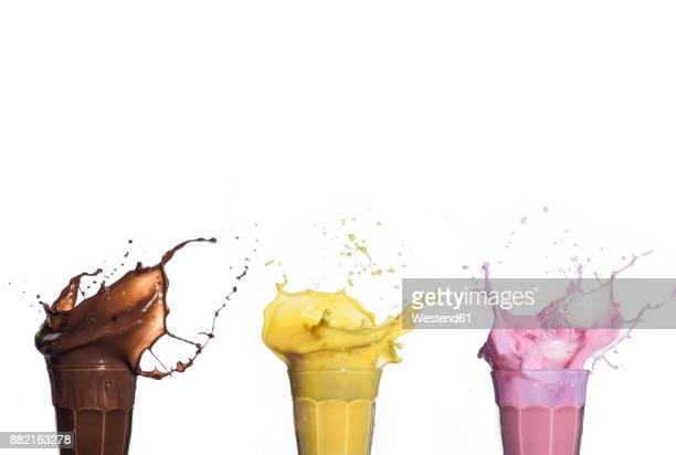 shakes of different flavors exploding on white background - exploding glass stock photos and pictures