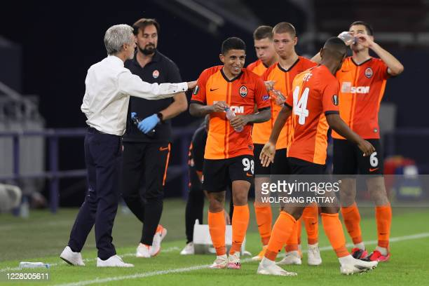 Shakhtar Donetsk's Brazilian midfielder Dodo is congratulated by Shakhtar Donetsk's Portuguese coach Luis Castro after scoring a goal during the UEFA...