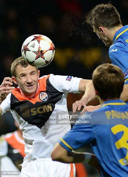 Shakhtar Donetsk's Olexandr Kucher heads the ball with BATE Borisov's Denis Polyakov and Aleksandr Karnitski during the UEFA Champions League group H...
