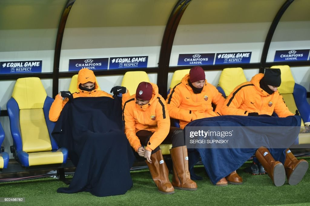 Shakhtar Donetsk's players keep warm with blankets and large boots during the UEFA Champions League round of 16 first leg football match between Shaktar Donetsk and AS Rome at the OSK Metalist Stadion in Kharkiv on February 21, 2018. Shakhtar Donetsk won the match 2-1. /