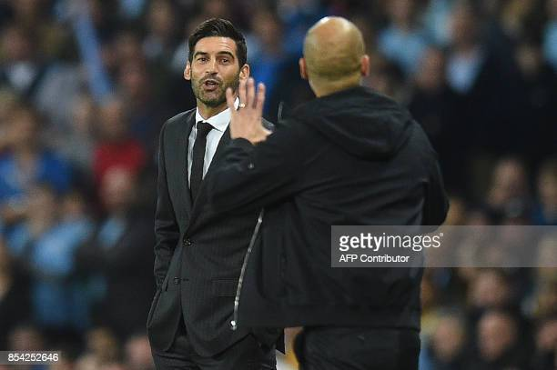 Shakhtar Donetsk's Portuguese manager Paulo Fonseca talks with Manchester City's Spanish manager Pep Guardiola following a tackle by Manchester...