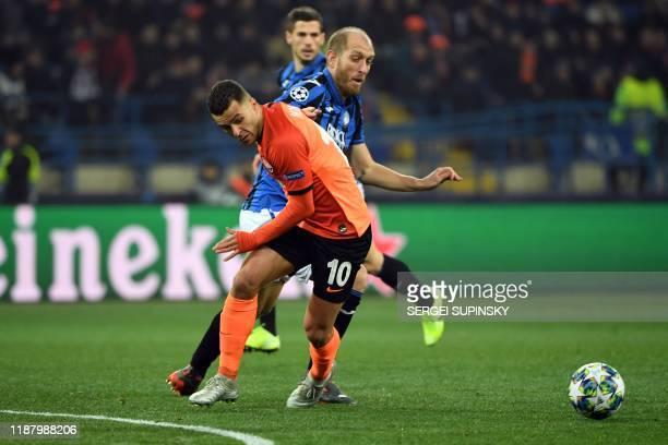 Shakhtar Donetsk's Ukrainian forward Junior Moraes and Atalanta's Italian defender Andrea Masiello vie for the ball during the UEFA Champions League...