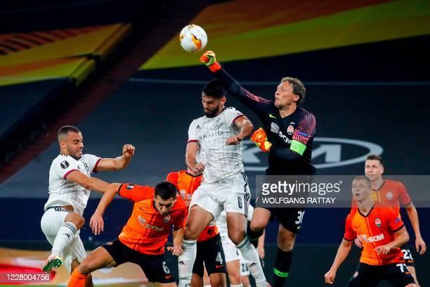 Shakhtar Donetsk's Ukrainian goalkeeper Andrey Pyatov pushes the ball next to FC Basel's Paraguayan defender Omar Alderete during the UEFA Europa...