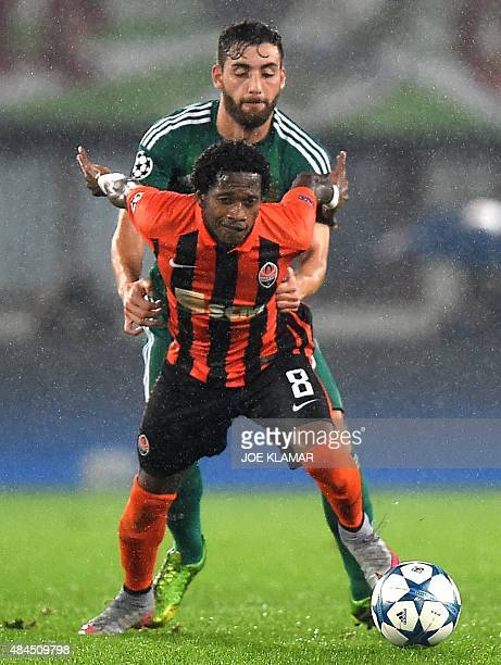 Shakhtar's Brazilian defender Fred and Rapid Vienna's Greek midfielder Thanos Petsos vie for the ball during the UEFA Champions League play off first...