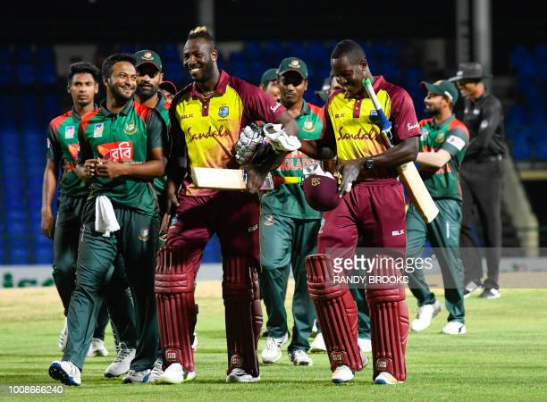 Shakib Al Hasan of Bangladesh Andre Russell and Rovman Powell of West Indies smile at the end of the 1st T20i match between West Indies and...