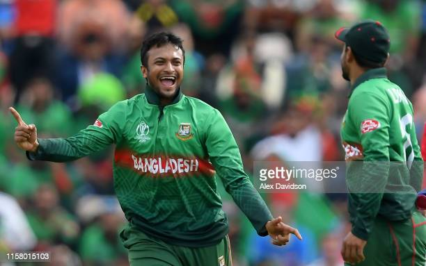 Shakib Al Hasan of Bangladesh celebrates the wicket of Gulbadin Naib of Afghanistan with Liton Das of Bangladesh during the Group Stage match of the...