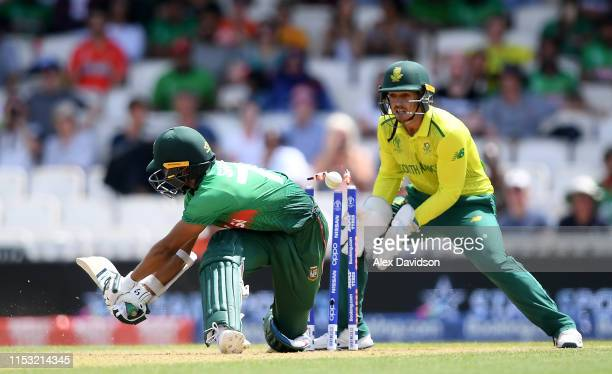 Shakib Al Hasan of Bangladesh is bowled by Imran Tahir of South Africa as Quinton De Kock of South Africa looks on during the Group Stage match of...
