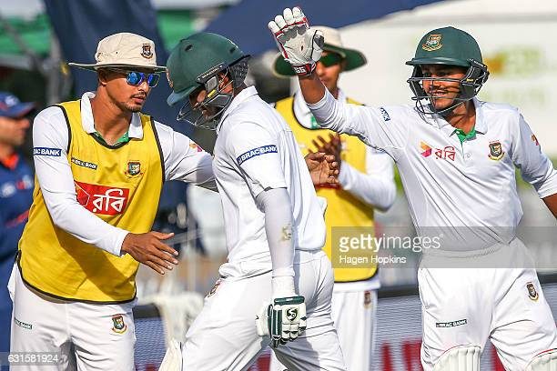 Shakib Al Hasan of Bangladesh is congratulated by teammates as he leaves the field after being dimissed for 217 during day two of the First Test...