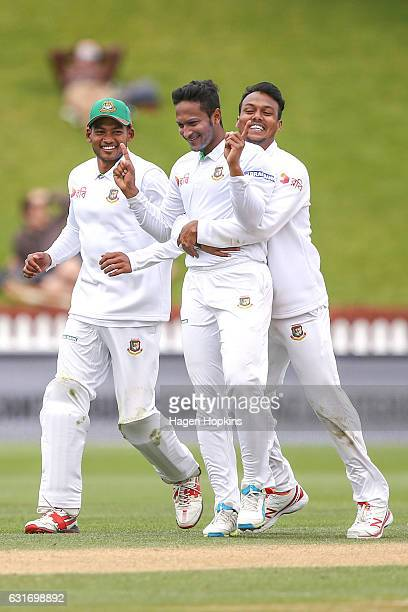 Shakib Al Hasan of Bangladesh is congratulated by teammates Nazmul Hossain Shanto and Kamrul Islam Rabbi after taking the wicket of Tom Latham of New...