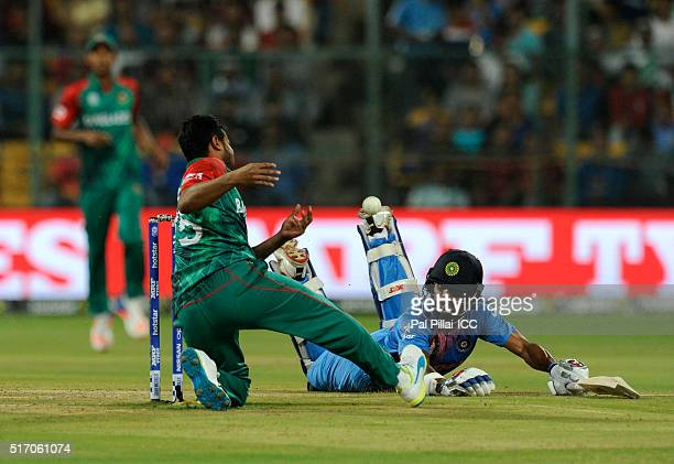 Shakib Al Hasan of Bangladesh misses a ball as Shikhar Dhawan of India jumps to make his ground during the ICC World Twenty20 India 2016 match...