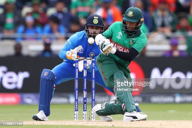 Shakib Al Hasan of Bangladesh scoops a shot to the legside as India wicketkeeper Rishabh Pant looks on during the Group Stage match of the ICC...