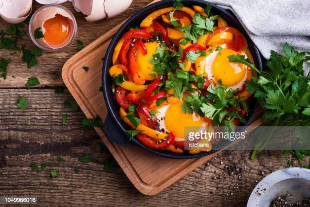 shakshouka, fried eggs cooked in bell peppers sauce - roasted pepper stock photos and pictures