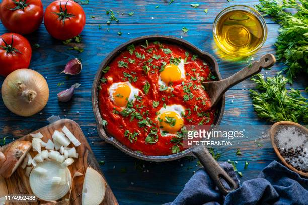 shakshouka poached eggs on tomato sauce - tomato sauce stock pictures, royalty-free photos & images