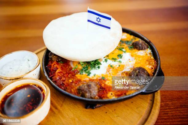 shakshouka with meatballs served with pita and decorated with israeli flag - israel bildbanksfoton och bilder