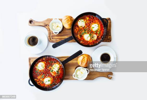 Shakshuka in a skillet served on the table for two persons