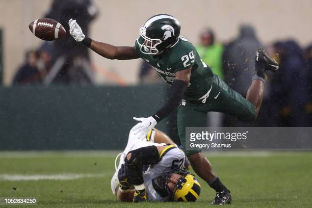 Shakur Brown of the Michigan State Spartans fumbles the ball during a punt return while being tackled by Jordan Glasgow of the Michigan Wolverines at...