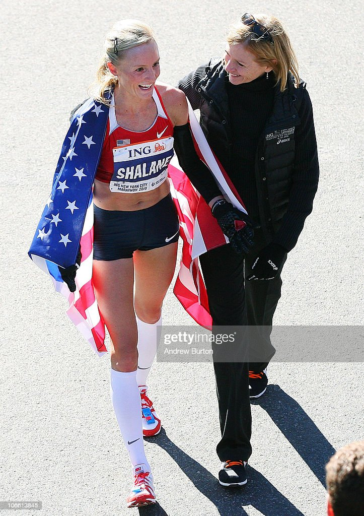 Shalane Flanagan #108 of the United States walks with Mary Wittenberg, president and CEO of New York Road Runners, after earning second place in the women's division of the 41st ING New York City Marathon on November 7, 2010 in New York City.