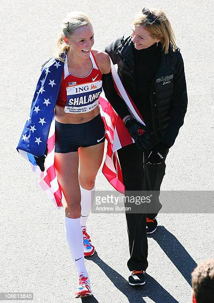 Shalane Flanagan of the United States walks with Mary Wittenberg, president and CEO of New York Road Runners, after earning second place in the...