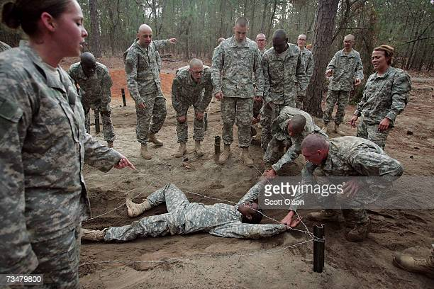 Shalish Grant of Jersey City New Jersey is helped through an obstacle course during Army basic training at Fort Jackson March 1 2007 in Columbia...