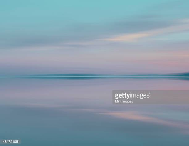 Shallow water over the surface at the Bonneville Salt Flats near Wendover, at dusk. Blurred motion. Pink sunset sky.