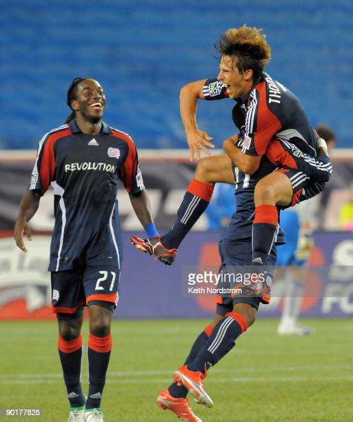 Shalrie Joseph looks on as Wells Thompson of the New England Revolution jumps into the arms of teammate Kheli Dube as he celebrates his goal against...