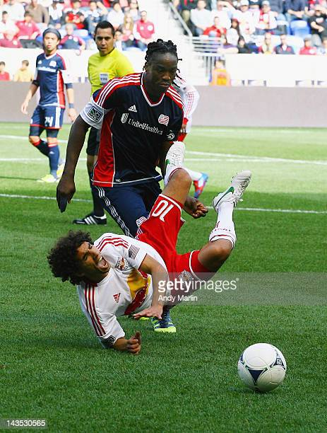 Shalrie Joseph of the New England Revolution trips up Mehdi Ballouchy of the New York Red Bulls during the game at Red Bull Arena on April 28 2012 in...