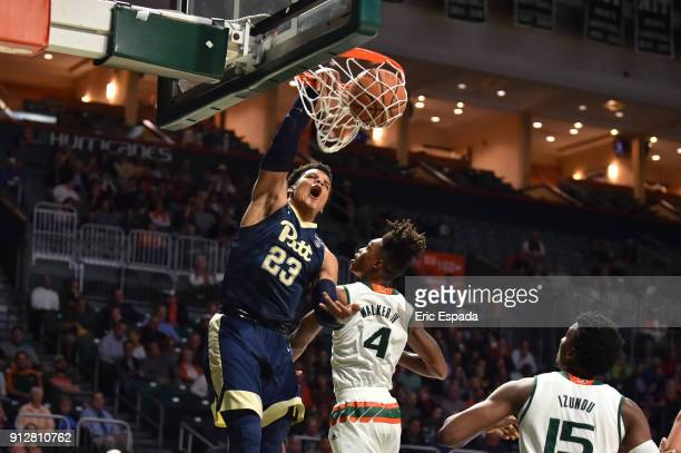 Shamiel Stevenson of the Pittsburgh Panthers dunks the basketball while being defended by Lonnie Walker IV of the Miami Hurricanes during the first...
