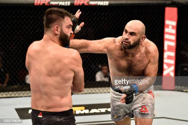 Shamil Abdurakhimov of Russia punches Andrei Arlovski of Belarus in their heavyweight bout during the UFC Fight Night event at Olimpiysky Arena on...