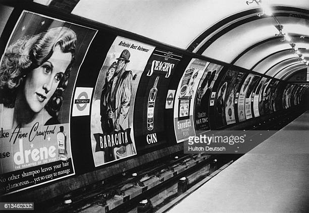 Shampoo raincoats and gin are some of the products advertised in the posters that line the tunnel wall at the Piccadilly underground station London...