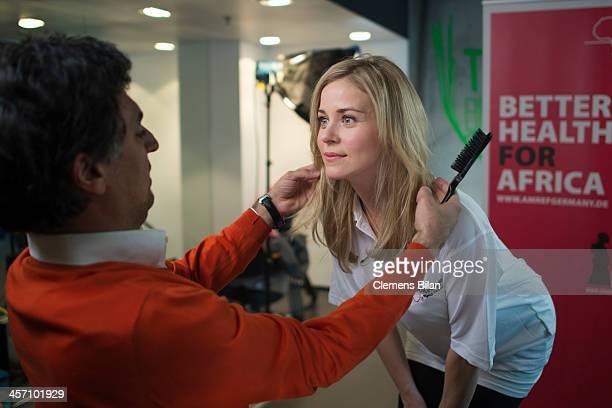 Shan Rahimkhan dresses the hair of Jessica Ginkel during a shoot for AMREF in Salon Shan Rahimkhan on December 16 2013 in Berlin Germany