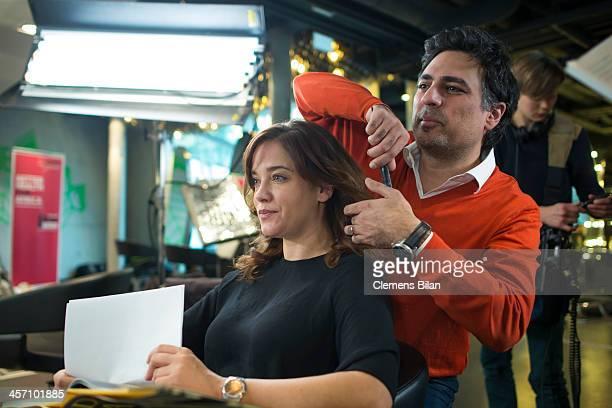 Shan Rahimkhan dresses the hair of Muriel Baumeister during a shoot for AMREF in Salon Shan Rahimkhan on December 16 2013 in Berlin Germany