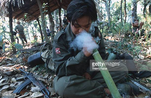Shan State Army soldier smokes tobacco through a bamboo water pipe during a rest stop on a relief mission