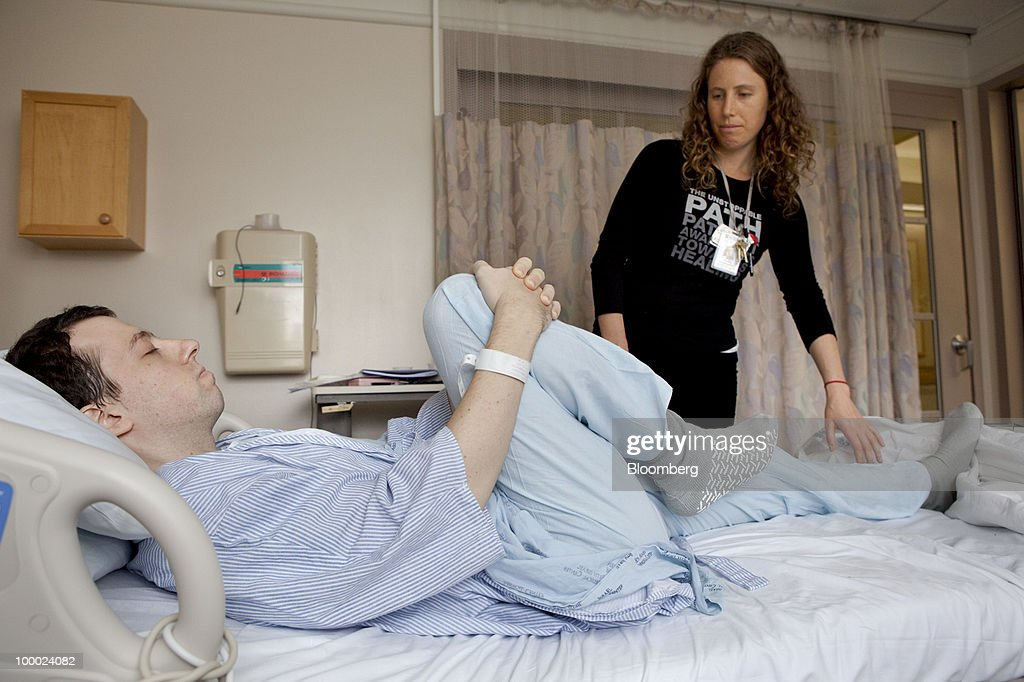 Shana Kuhn-Siegel, a yoga instructor, leads David Goldberg, a 30-year-old leukemia patient, through a yoga routine in his hospital bed at Beth Israel hospital in New York, U.S., on Wednesday, May 19, 2010. Yoga doesnÕt cure cancer, but its stretching and breathing exercises did improve sleep, reduce dependence on sedatives and enable cancer patients to better resume the routine activities of everyday life, according to a 410-patient study being highlighted at the American Society of Clinical OncologyÕs annual meeting in Chicago next month. Photographer: JB Reed/Bloomberg via Getty Images