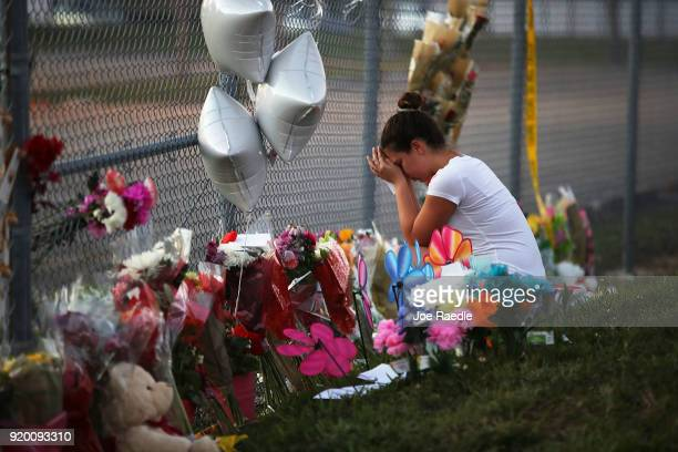 Shana Rosenthal a student at Marjory Stoneman Douglas High School visits a makeshift memorial setup in front of the school on February 18 2018 in...