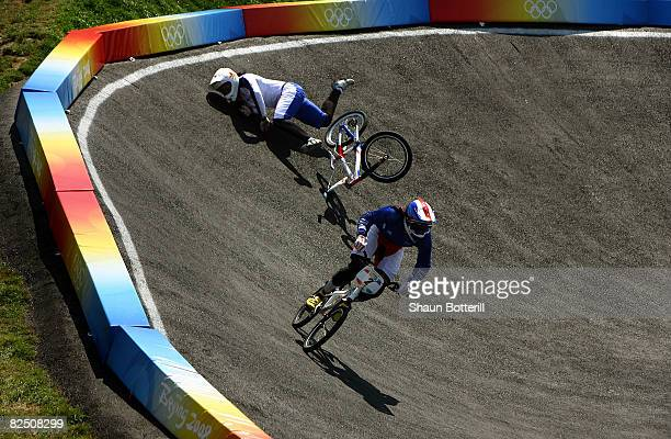 Shanaze Reade of Great Britain crashes as Anne-Caroline Chausson of France races en route to the gold medal in the Women's BMX final run held at the...