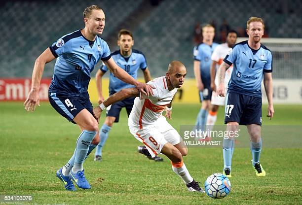 Shandong Luneng player Diego Tardelli Martins evades the tackle of Sydney FC player Zac Anderson as David Carney looks on during their AFC Champions...