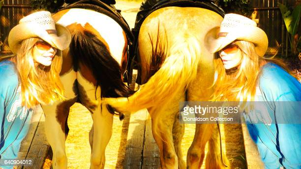 Shane Barbi and Sia Barbi of the Barbi Twins pose for a portrait behind horses in circa 2000 in Los Angeles California