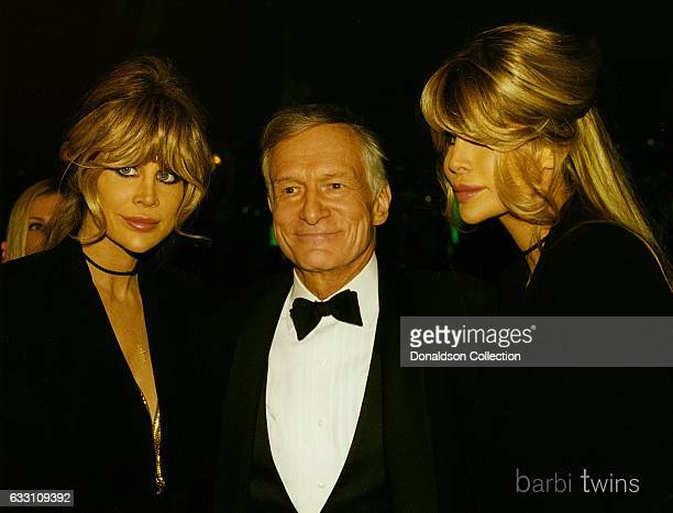 Shane Barbi and Sia Barbi of The Barbi Twins pose for a portrait with Hugh Hefner in circa 1995