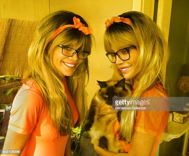 Shane Barbi and Sia Barbi of The Barbi Twins pose for a portrait with a cat in circa 1995