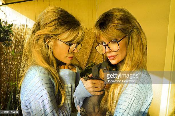 Shane Barbi and Sia Barbi of The Barbi Twins pose for a portrait with a dog in circa 1995