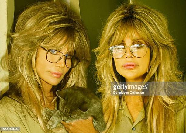 Shane Barbi and Sia Barbi ofThe Barbi Twins pose for a portrait with a cat in circa 1995