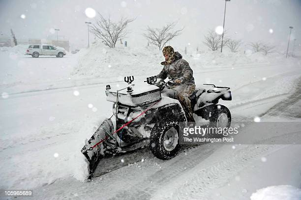 Shane Beavers plows in front of an open grocery store as a blizzard hits the DC regional area in Dunkirk MD on February 6 2010 The storm is set to...