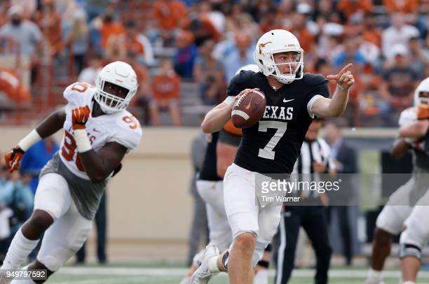 Shane Buechele of the Texas Longhorns looks to pass under pressure by Charles Omenihu in the first half during the OrangeWhite Spring Game at Darrell...