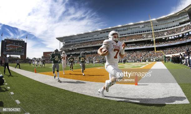 Shane Buechele of the Texas Longhorns runs through the end zone scoring a touchdown as Jameson Houston and Verkedric Vaughns of the Baylor Bears...