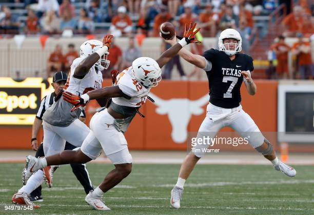 Shane Buechele of the Texas Longhorns throws a pass under pressure by Marqez Bimage and Charles Omenihu in the first half during the OrangeWhite...