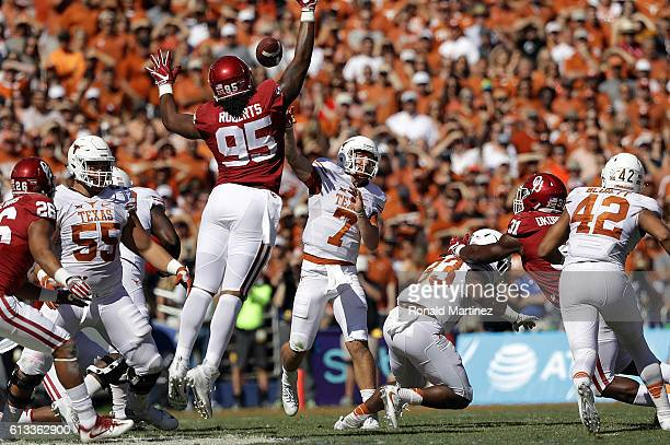 Shane Buechele of the Texas Longhorns throws over Austin Roberts of the Oklahoma Sooners at Cotton Bowl on October 8 2016 in Dallas Texas