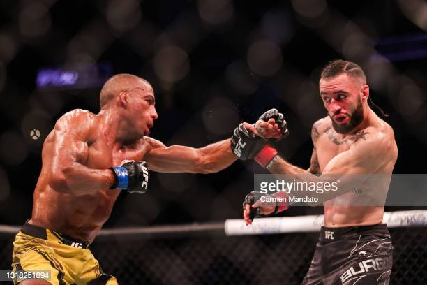 Shane Burgos defends a punch from Edson Barboza of Brazil during their featherweight bout at the UFC 262 event at Toyota Center on May 15, 2021 in...
