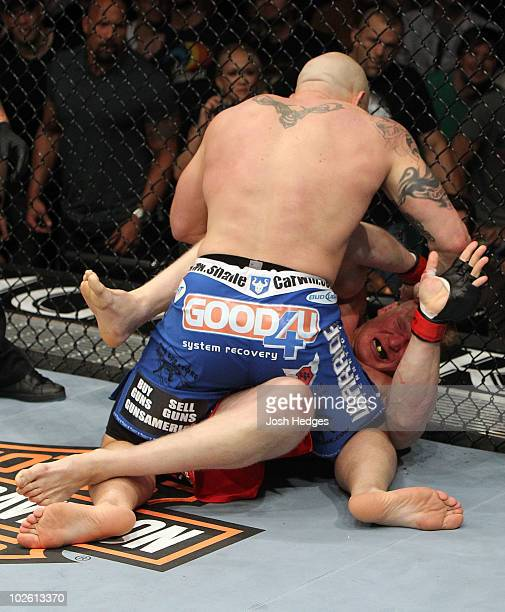 Shane Carwin holds down Brock Lesnar in the first round during the UFC Heavyweight Championship Unification bout at the MGM Grand Garden Arena on...